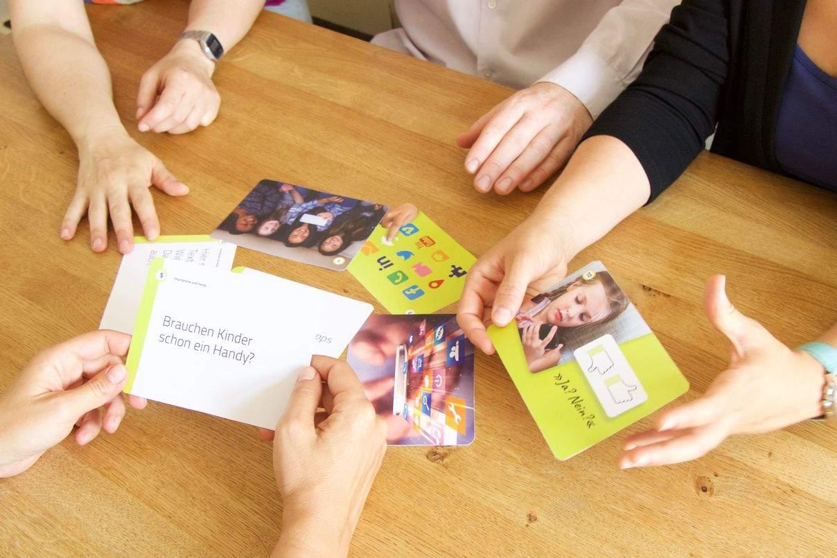 Hände von Eltern halten Karten